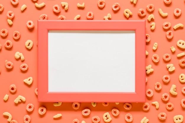 Maquette cadre vierge et céréales de petit déjeuner sur une surface colorée Photo gratuit