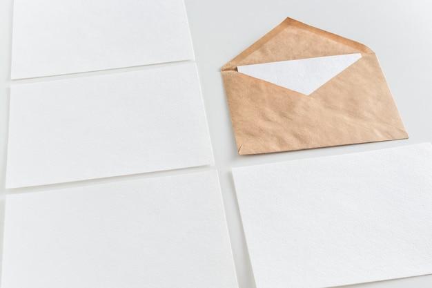 Maquette de cartes de visite horizontales et enveloppe de l'artisanat à fond blanc. Photo Premium