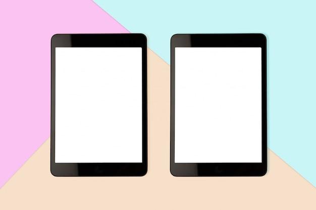 Maquette deux tablette numérique avec un écran blanc sur fond de couleur pastel, photo plat laïc Photo Premium