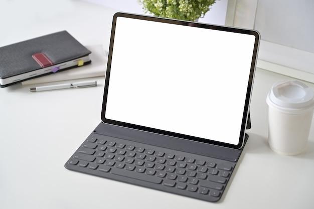 Maquette écran vide tablette avec clavier intelligent sur la table de l'espace de travail. Photo Premium