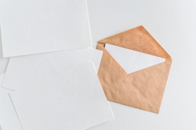Maquette d'enveloppe et de papier blanc vierge sur fond blanc Photo Premium