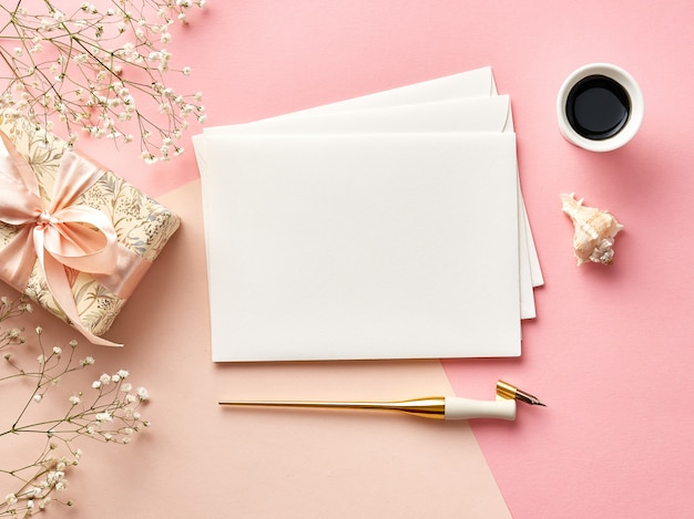 Maquette d'enveloppes vierges sur fond rose ou beige avec calligraphie Photo Premium
