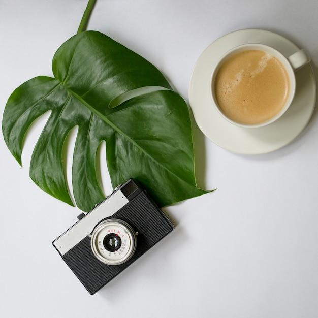 Maquette d'espace de travail avec feuille de palmier tropical, cahier, appareil photo, stylo, carte et tasse à café Photo Premium
