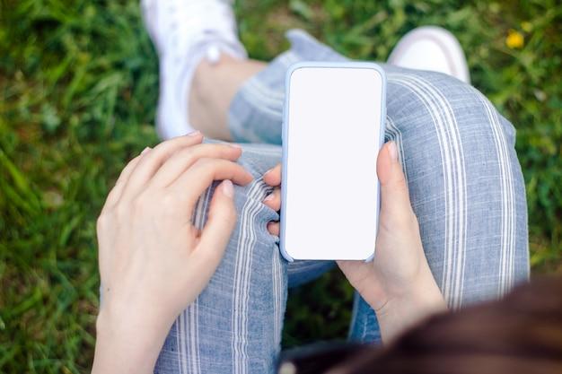 Maquette de femme main tenant un téléphone portable avec écran blanc Photo Premium