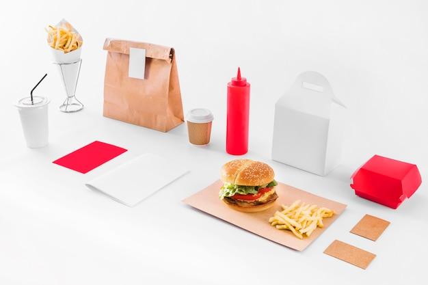 Maquette de hamburger; frites; parcelle; bouteille de sauce et tasse d'élimination sur fond blanc Photo gratuit
