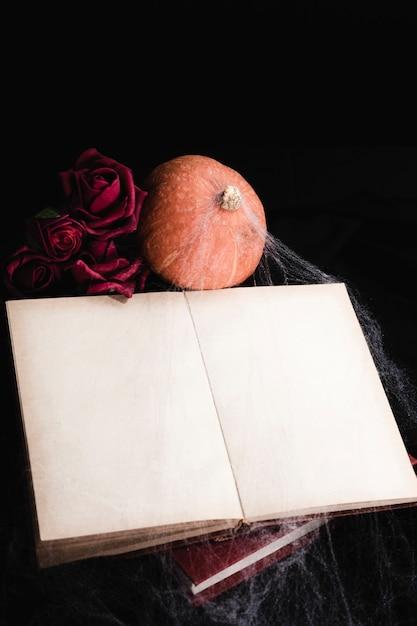 Maquette de livre avec roses et citrouille Photo gratuit
