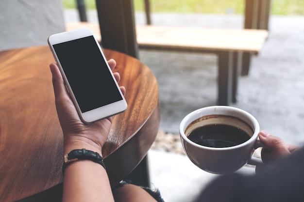 Maquette de mains tenant un téléphone portable blanc avec un écran noir vide tout en buvant du café Photo Premium