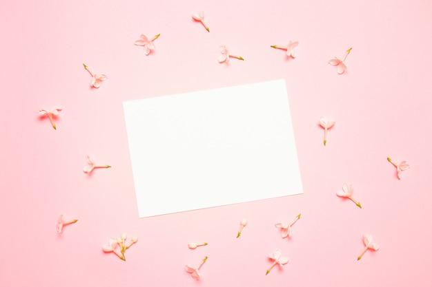 Maquette de mariage avec liste de papier blanc et fleurs sur fond bleu Photo Premium