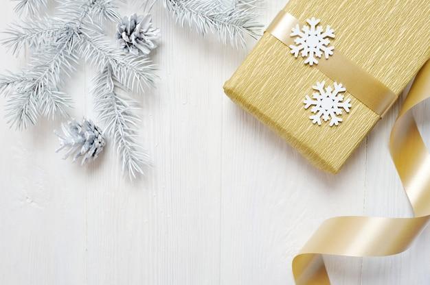 Maquette noël cadeau doré arc et arbre cône, flatlay sur un blanc en bois Photo Premium