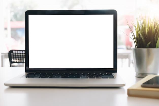 Maquette ordinateur portable écran blanc sur le bureau dans le fond de la salle de bureau Photo Premium