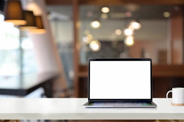 Maquette ordinateur portable à écran blanc sur une table de bureau blanche au bureau Photo Premium