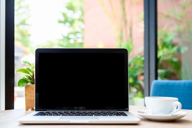 Maquette D'ordinateur Portable Avec écran Vide Avec Tasse De Café Sur La Table Du Café, écran Noir Photo Premium