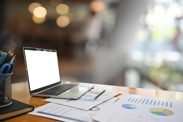 Maquette ordinateur portable sur la table de travail avec écran vide. Photo Premium