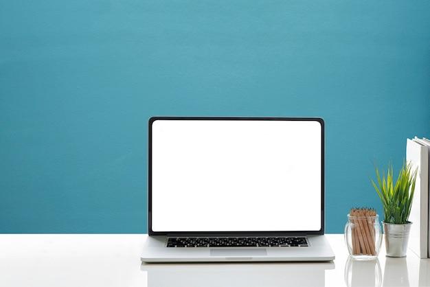 Maquette de portable avec écran blanc et fournitures sur tableau blanc. Photo Premium