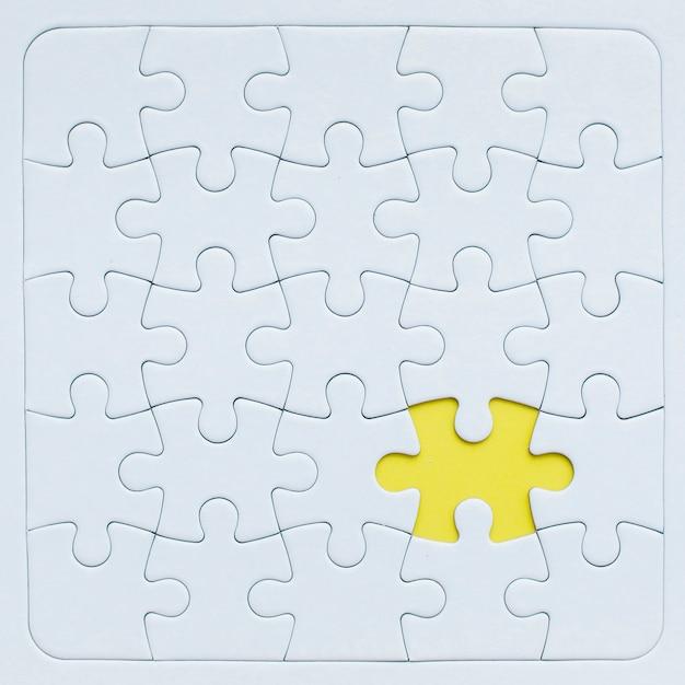 Maquette de puzzle avec pièce jaune. Photo gratuit