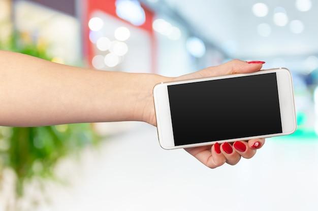 Maquette smartphone avec écran blanc dans les mains de la femme Photo Premium