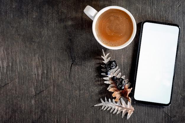 Maquette smartphone avec écran blanc et des écouteurs sur fond en bois. Photo Premium