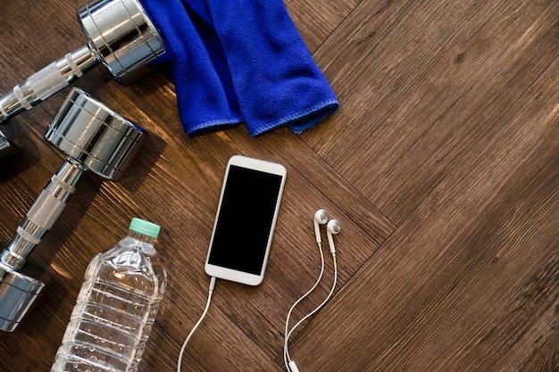 Maquette smartphone avec haltère, bouteille et écouteurs en métal Photo Premium