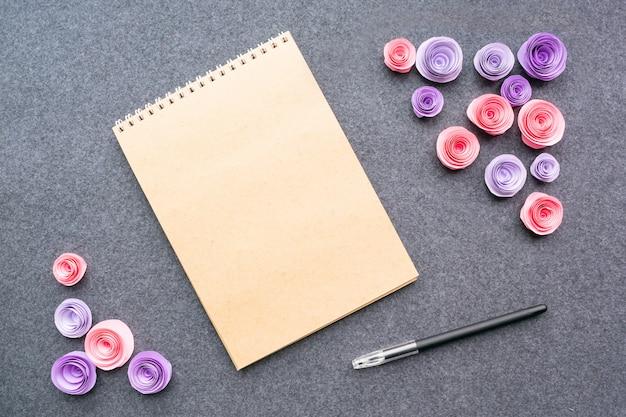 Maquette avec un stylo cahier vide et des roses roses en papier Photo Premium