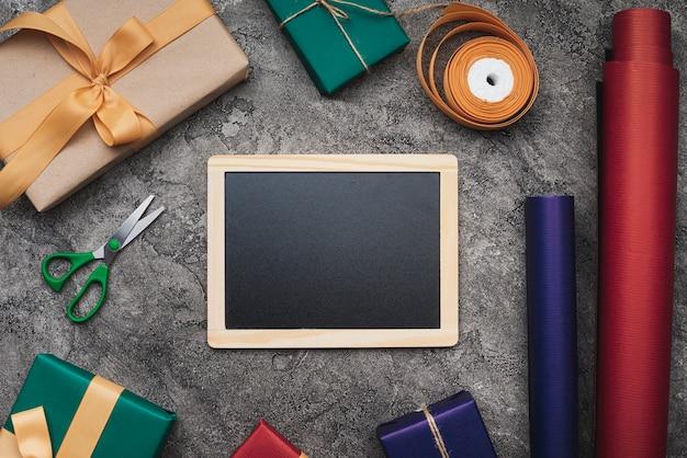 Maquette de tableau noir sur fond texturé avec des cadeaux et du papier d'emballage Photo gratuit