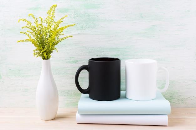 Maquette De Tasse Blanche Et Noire Avec De L'herbe à Fleurs Vertes Ornementales Photo Premium