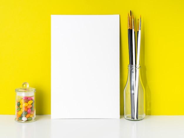 Maquette en toile blanche, bonbons dans un bocal, pinceaux sur fond jaune vif. concept Photo Premium