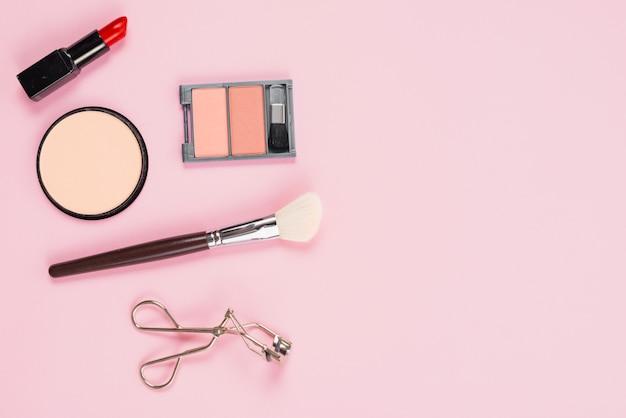 Maquillage et accessoires cosmétiques mise en page sur fond rose Photo gratuit