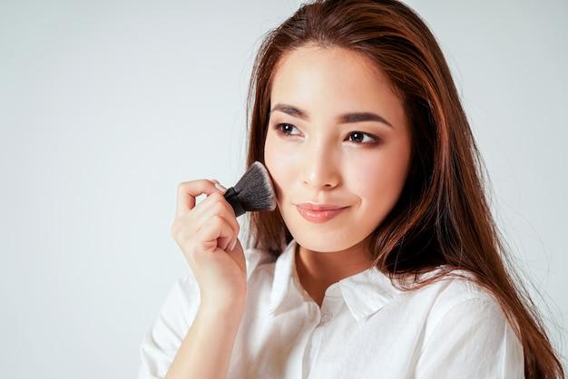 Maquillage brosse kabuki dans la main de la souriante jeune femme asiatique aux cheveux longs noirs Photo Premium