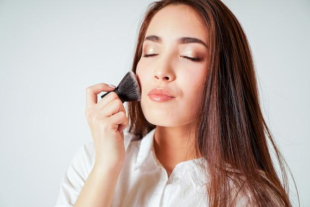 Maquillage brosse kabuki dans la main de la souriante jeune femme asiatique avec de longs cheveux noirs sur blanc Photo Premium