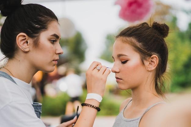 Maquillage classe de maître. fille se maquille à son amie Photo gratuit