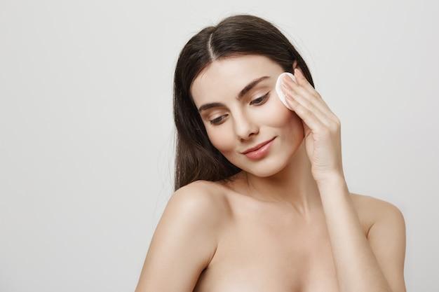Maquillage De Décollage Femme Mignonne Souriante Avec Un Coton Photo gratuit