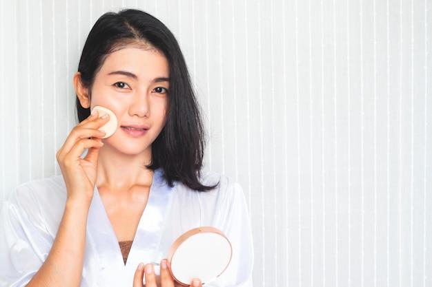 Maquillage Du Visage. Belle Femme Asiatique Appliquant De La Poudre Sur Le Visage Photo Premium