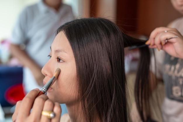 Maquillage de fille en utilisant un artiste de maquillage professionnel. Photo gratuit