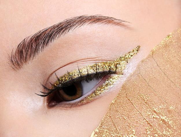 Maquillage De Mode En Flèche Eye-liner Doré Sur La Femelle Avec Une Feuille Jaune Photo gratuit