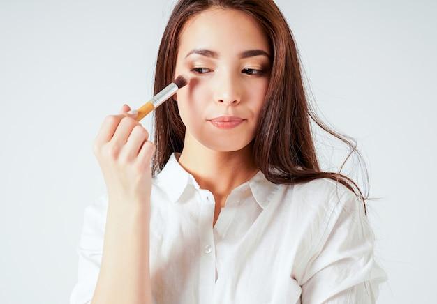 Maquillage pinceau dans la main de la jeune femme asiatique souriante aux cheveux long noir sur fond blanc Photo Premium