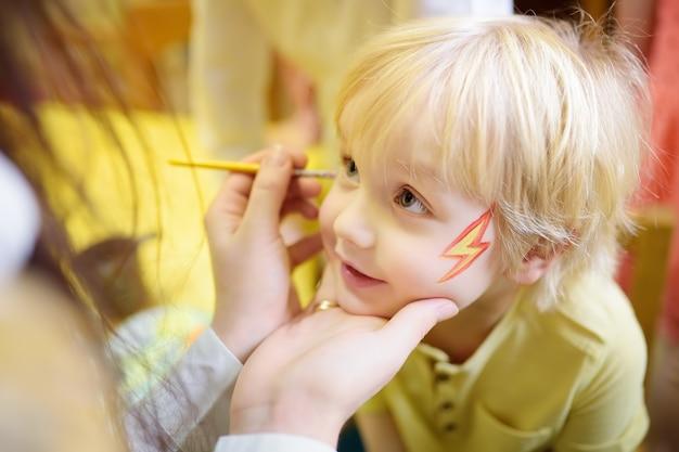 Maquillage pour un mignon petit garçon pendant la joie des enfants. Photo Premium