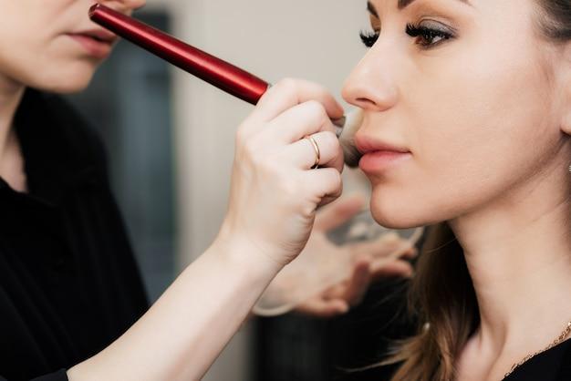 Maquillage Sur Le Visage D'une Femme Dans Un Salon De Beauté Fait Une Main De Maquilleuse Avec Une Brosse Photo Premium