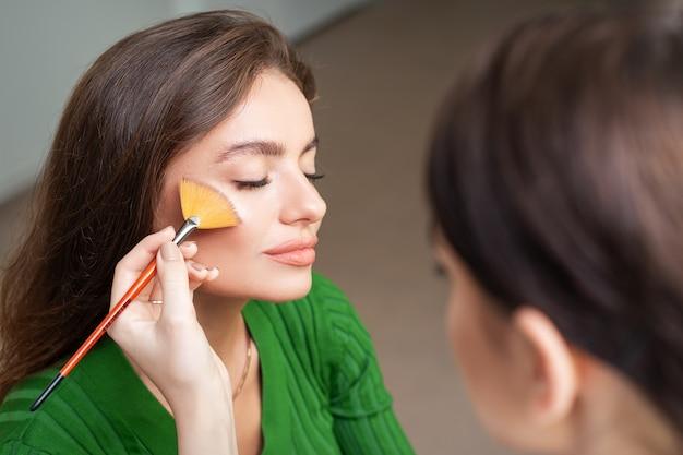 Maquilleur Appliquant Un Maquillage Professionnel De Fond De Teint Sur Le Visage De La Belle Jeune Femme Caucasienne Dans La Salle De Maquillage. Base Pour Le Maquillage. Photo Premium