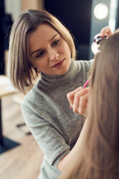 Maquilleur applique eyeliner sur le modèle de culture Photo gratuit