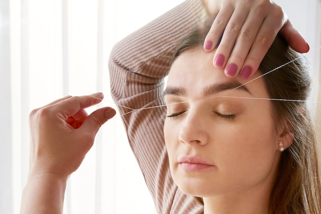 Le Maquilleur épile Les Sourcils Avec Un Gros Plan De Fil. Soins Du Visage Soins De Beauté Dans Le Salon De Beauté Photo Premium