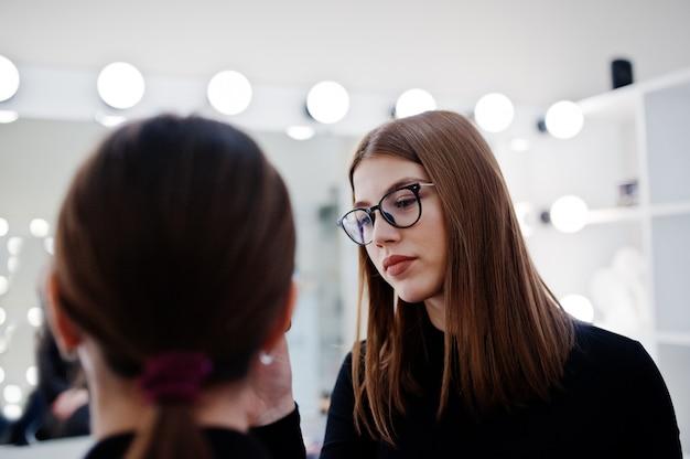 Maquilleur Travaille Dans Son Salon Studio Beauté Visage. Femme Postulant Par Maître De Maquillage Professionnel. Photo Premium