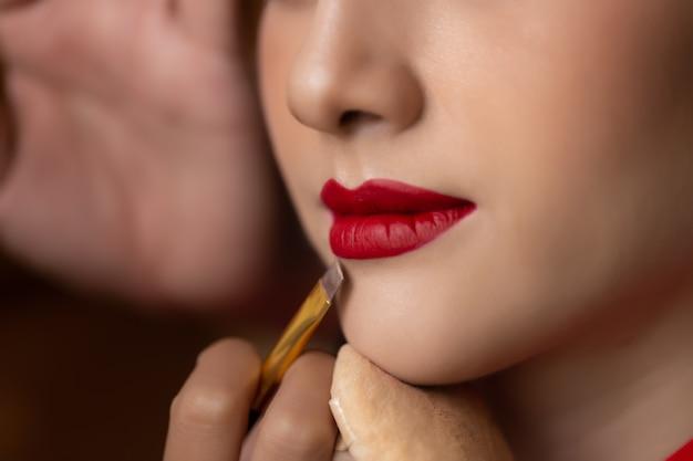 Maquilleuse appliquer un rouge à lèvres sur la bouche d'un beau modèle à l'aide d'un pinceau Photo Premium