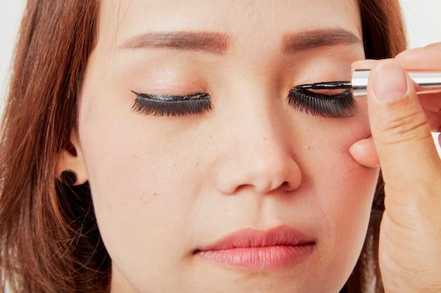 La maquilleuse colle les cils au client Photo Premium