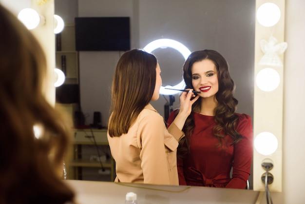 Maquilleuse Faisant Le Maquillage Professionnel De La Jeune Femme. Ecole Des Maquilleurs Photo Premium