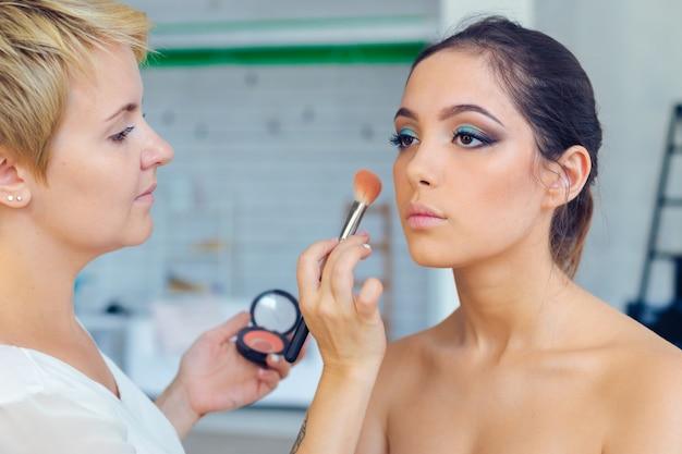 Maquilleuse faisant maquillage professionnel de jeune femme Photo Premium