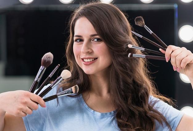 Maquilleuse femme heureuse avec des pinceaux Photo gratuit