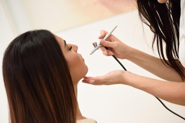 Maquilleuse utilisant un aérographe faisant un maquillage à l'aérographe Photo Premium