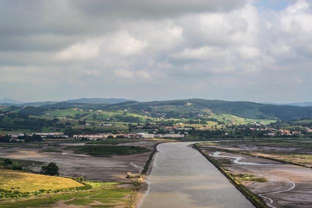 Marais d'une rivière parmi des collines verdoyantes Photo Premium