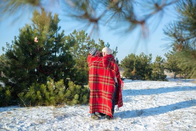En marchant en hiver dans les bois, un mec enveloppe sa petite amie dans un plaid chaud à carreaux rouges pour qu'elle se réchauffe Photo Premium