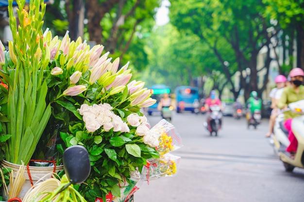 Marché aux fleurs et vélo sur la route dans le centre de hanoi vietnam composé de lilly. Photo Premium